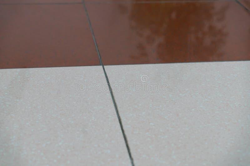Le mattonelle del granito sono marroni e bianche sul pavimento come i precedenti Struttura di granito immagine stock libera da diritti