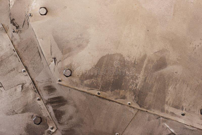 Le mattonelle dorate metalliche del blocco con i bulloni pavimentano la luce intensa di riflessione Concetto astratto industriale fotografie stock
