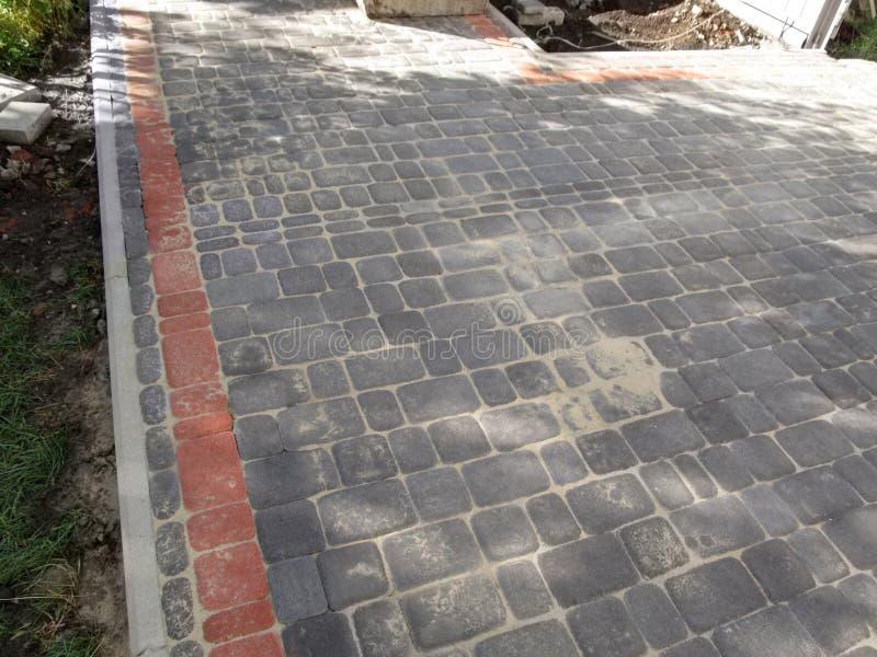 Le mattonelle grige e rosse recentemente poste della pavimentazione hanno orlato con i bordi nell'iarda fotografia stock