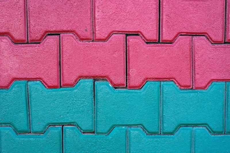 Le mattonelle rosse e verdi del blocchetto del marciapiede si chiudono sul colpo ad una casa residentual, immagine per fondo immagini stock