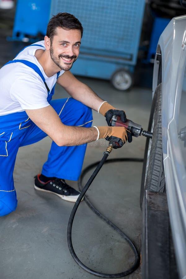 Le mekanikern som reparerar bilhjulet arkivbild
