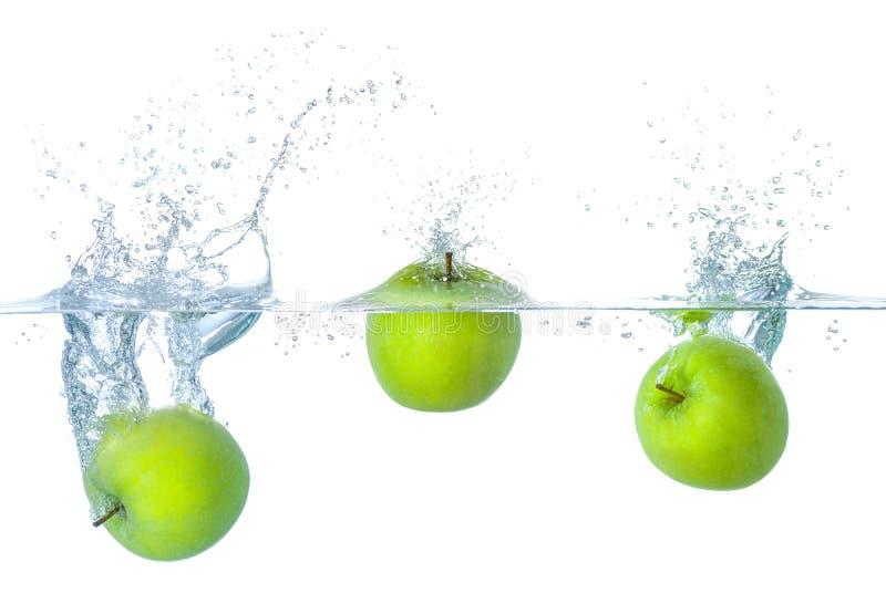 Le mele che cadono nell'acqua con spruzza fotografie stock