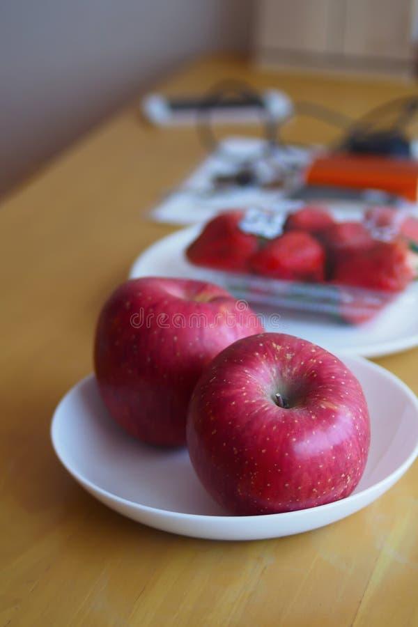 Le mele rosse in un piatto bianco sono disposte su una tavola di legno marrone immagini stock libere da diritti