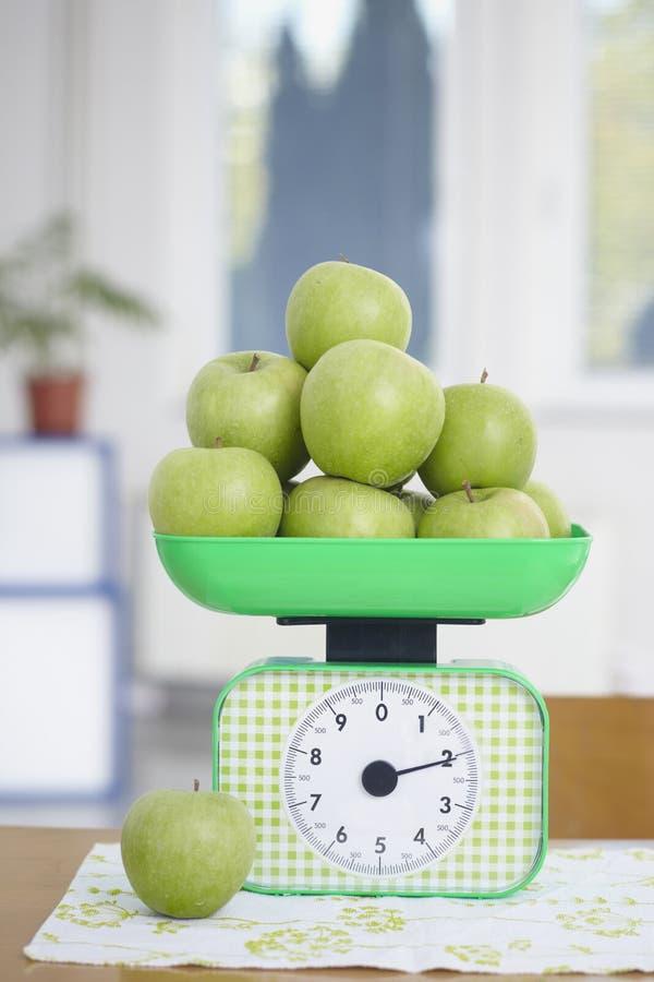 Le mele verdi sulla cucina riportano in scala la frutta dell'alimento fotografia stock