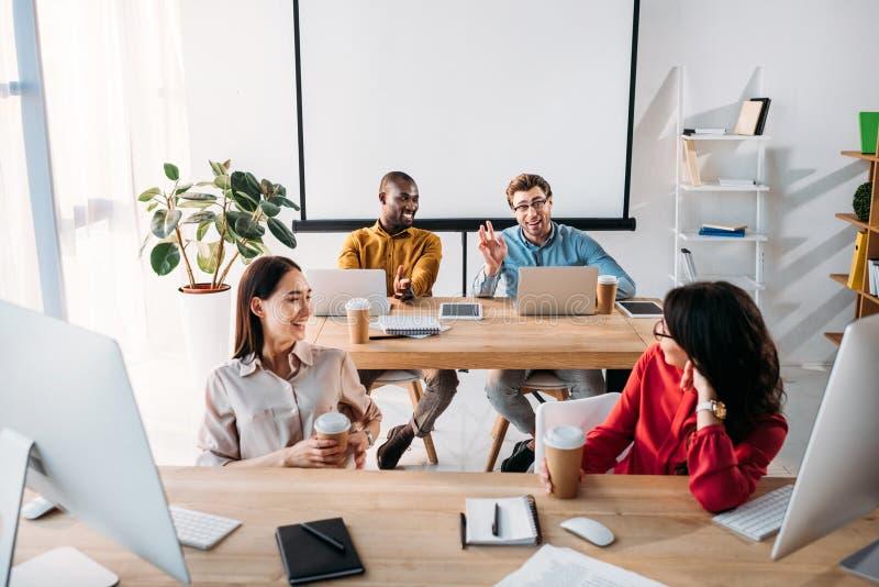 le mellan skilda raser ungt affärsfolk som talar under arbete arkivbilder