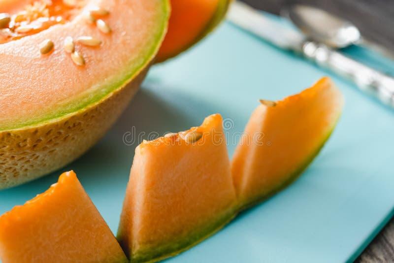Le melon orange de cantaloup découpe en tranches sur une fin de hachoir  images stock