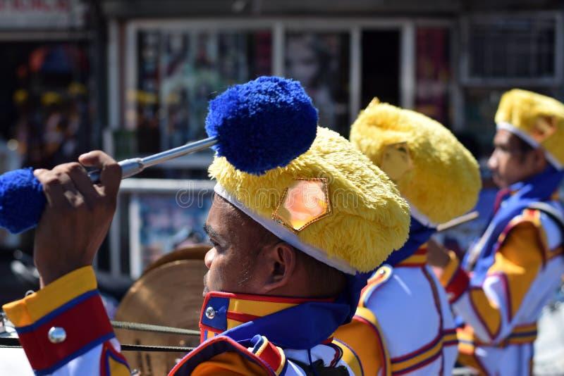 Le membre du groupe masculin joue le tambour pendant le cortège de festivité de ville image libre de droits