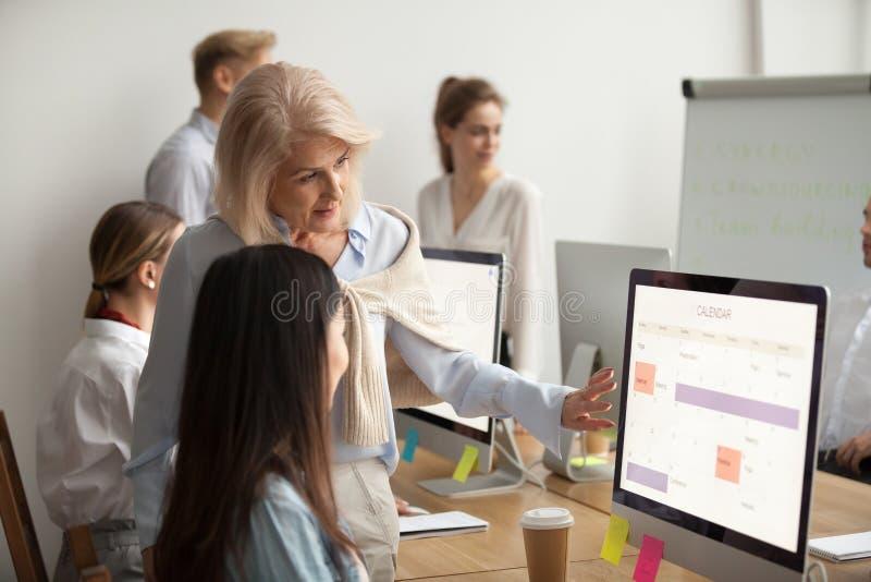 Le meneur d'équipe supérieur enseignant le nouvel employé explique le travail de planification photos libres de droits