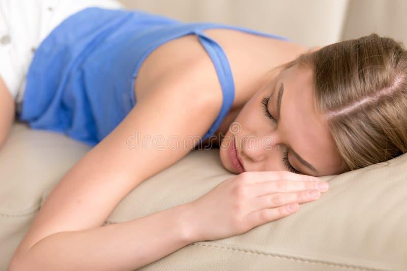 Le mensonge de femme de sommeil déshérité par jeunes endormi sur le sofa, se ferment  photos libres de droits
