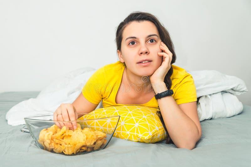 Le mensonge de femme sur le mauvais film de montre et mangent des snaks photo libre de droits