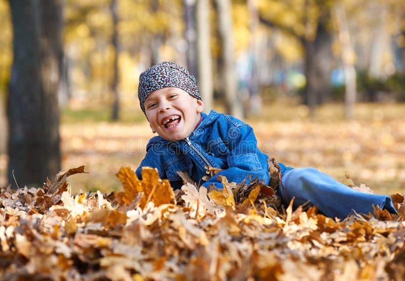 Le mensonge de garçon sur le jaune part dans le parc d'automne, le jour ensoleillé lumineux, feuilles tombées sur le fond image libre de droits
