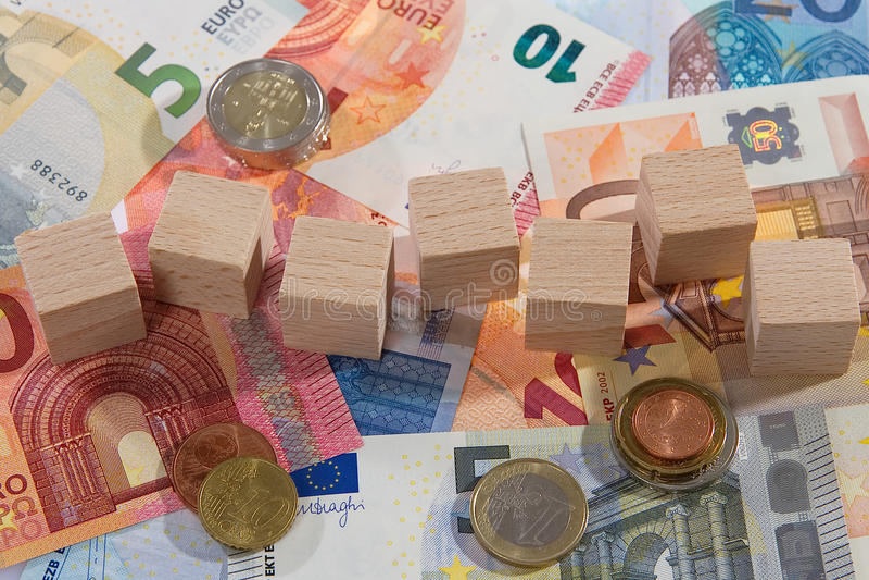 Le mensonge des billets de banque avec en bois découpe des pièces de monnaie images stock