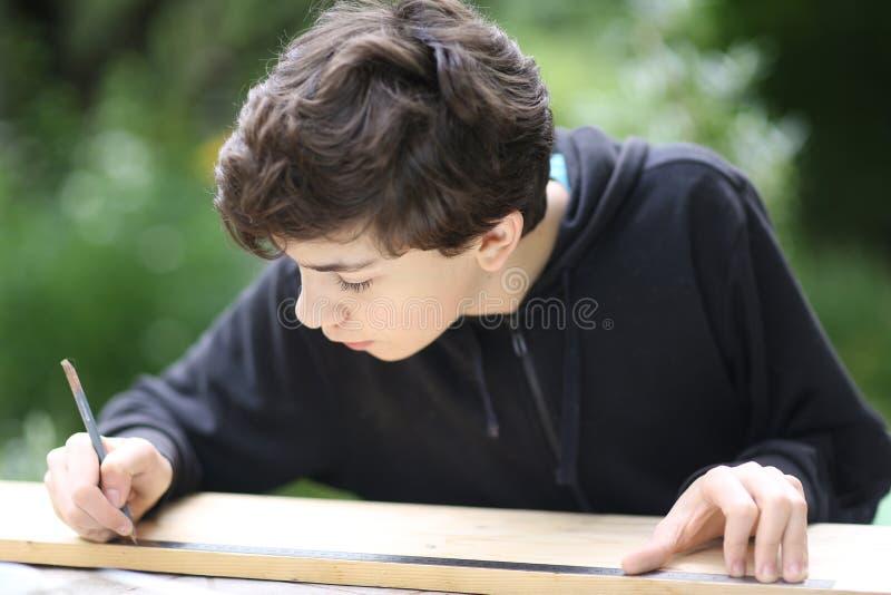Le menuisier adolescent mesure le bois pour faire des travaux ménagers images libres de droits