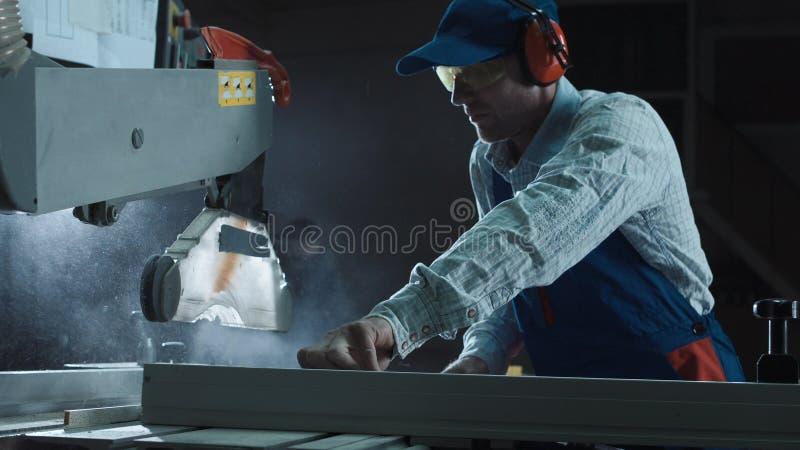 Le menuisier travaille à une machine de sawing photos libres de droits
