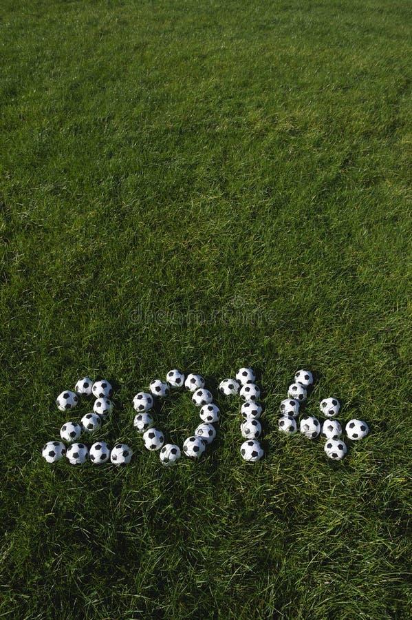 Le message pour 2014 a fait avec des ballons de football du football sur l'herbe photo libre de droits