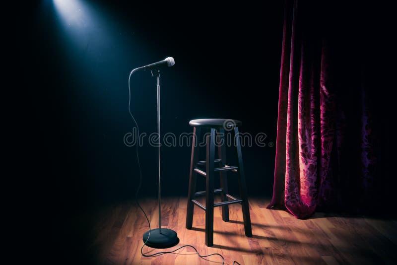 Le microphone et le tabouret en bois sur une étape de comédie de support avec des réflecteurs rayonnent, image contrastée photographie stock