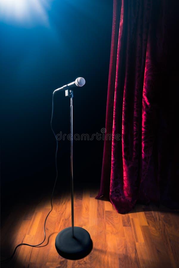 Le microphone sur une étape de comédie de support avec des réflecteurs rayonnent, image contrastée photographie stock
