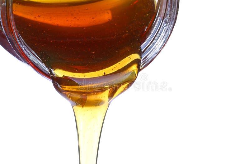 Le miel débordent le pot en verre d'isolement sur le blanc photo libre de droits