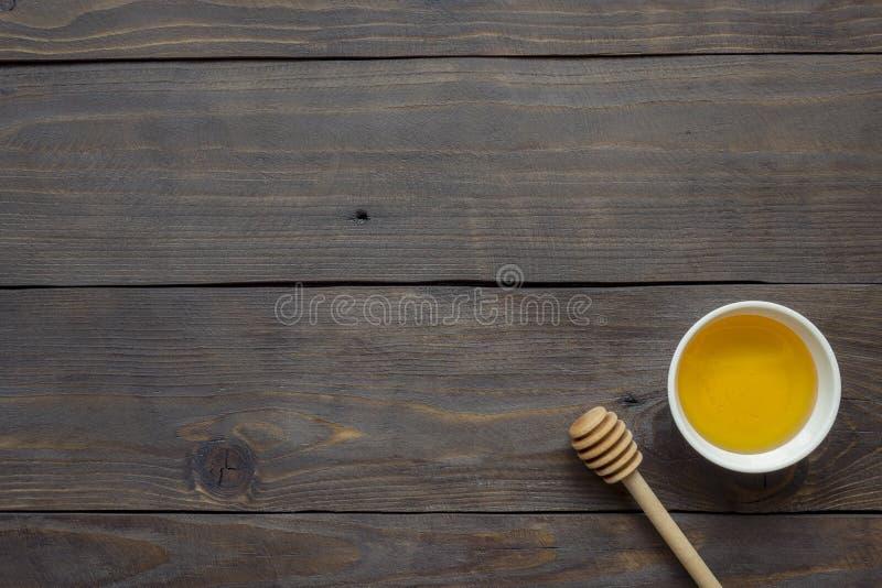 Le miel liquide dans le plat et le miel collent le fond en bois foncé images stock