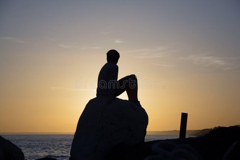 Le milford de lymington de coucher du soleil de paysage marin sur la mer avec la silhouette du garçon s'est reposé sur une roche image stock