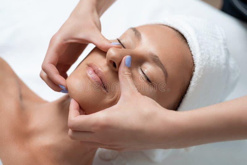 Le milieu attrayant a vieilli la dame recevant le massage de visage au salon de station thermale photo libre de droits