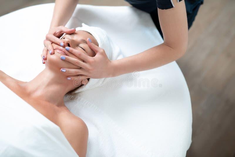 Le milieu avec du charme a vieilli la femme atteignant le massage de visage le salon de station thermale photographie stock