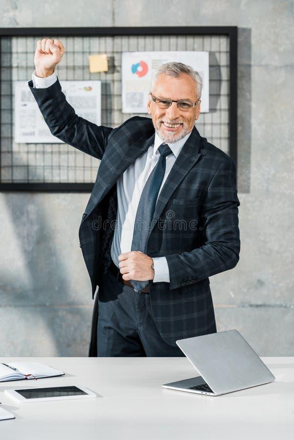 le milieu beau heureux a vieilli l'homme d'affaires faisant des gestes et regardant la caméra image libre de droits