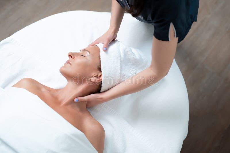 Le milieu calme a vieilli la femme atteignant le massage de visage et de cou le salon de station thermale photo stock