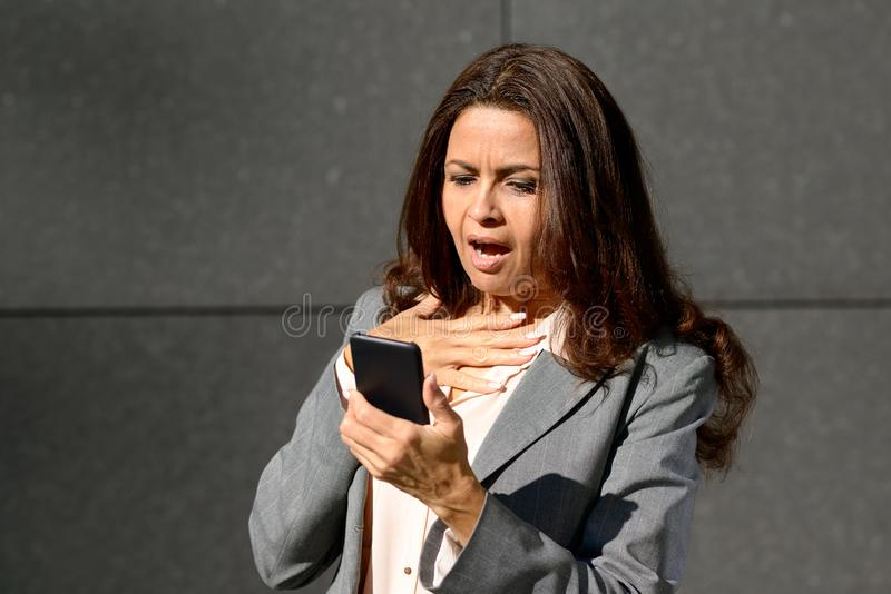 Le milieu choqué a vieilli la femme lisant un message textuel photos libres de droits