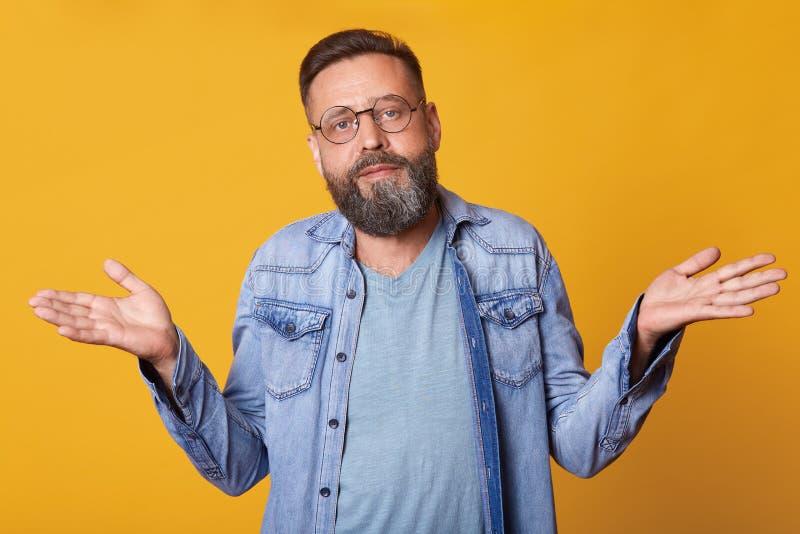 Le milieu désespéré désespéré a vieilli l'homme portant le T-shirt occasionnel bleu, la veste de jeans et les lunettes ronds à la photos libres de droits