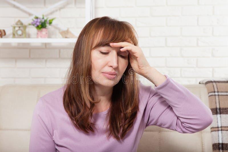 Le milieu de brune a vieilli la femme ayant le mal de tête sur le fond à la maison ménopause image stock