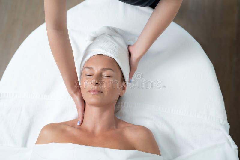 Le milieu de sourire a vieilli la dame appréciant le massage de cou au salon de station thermale photos stock