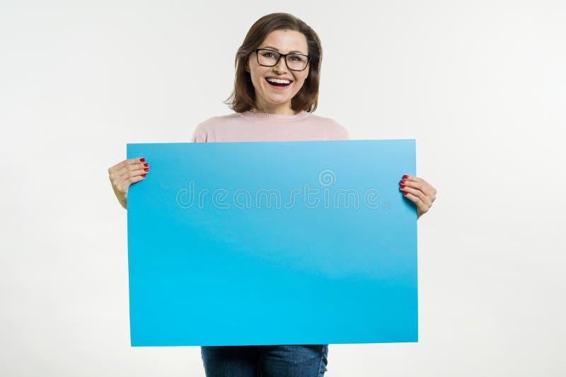 Le milieu de sourire a vieilli la femme avec le panneau d'affichage bleu de feuille photo libre de droits