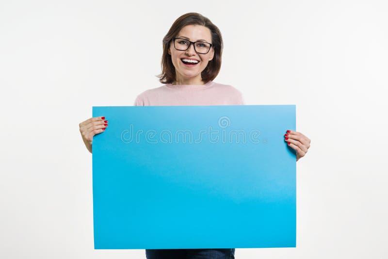 Le milieu de sourire a vieilli la femme avec le panneau d'affichage bleu de feuille image libre de droits