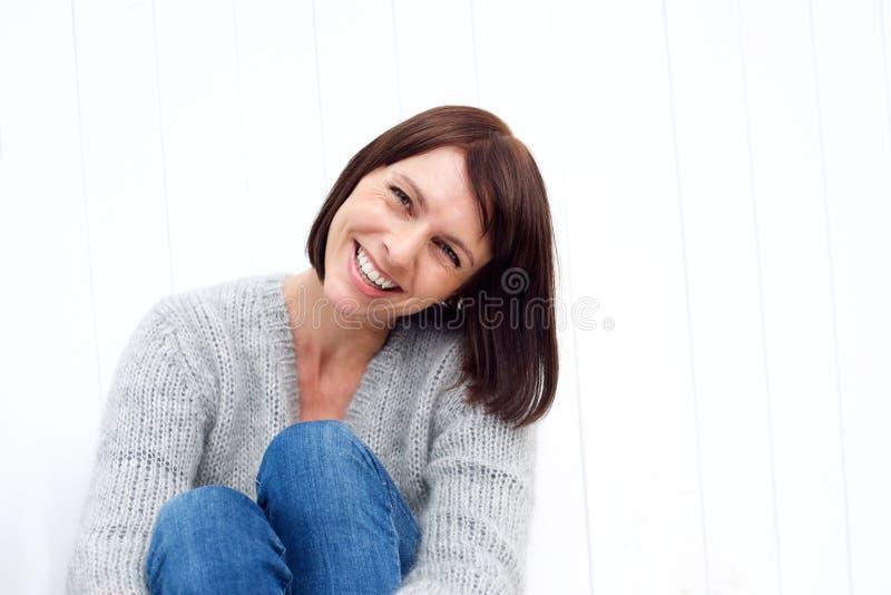Le milieu de sourire a vieilli la femme s'asseyant contre le mur blanc image libre de droits