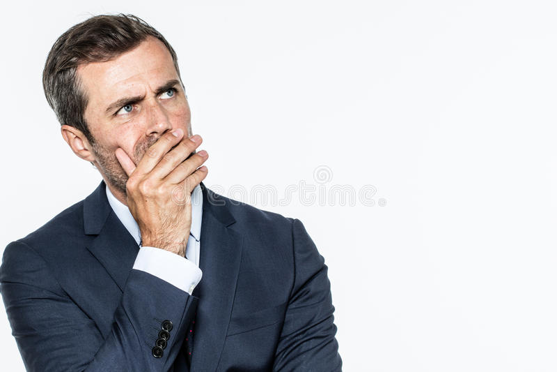 Le milieu futé a vieilli l'homme d'affaires pensant, recherchant, cachant sa bouche photo libre de droits