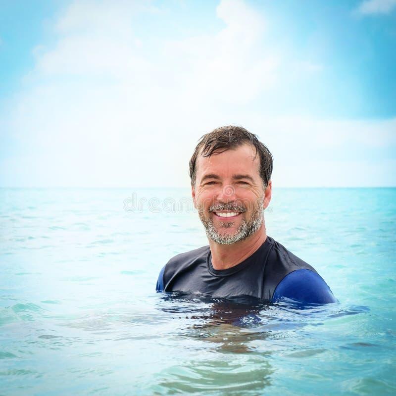 Le milieu heureux a vieilli l'homme barbu souriant dans l'océan photo libre de droits