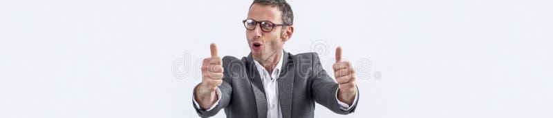 Le milieu heureux a vieilli l'homme d'affaires avec des lunettes et des pouces, bannière photo stock