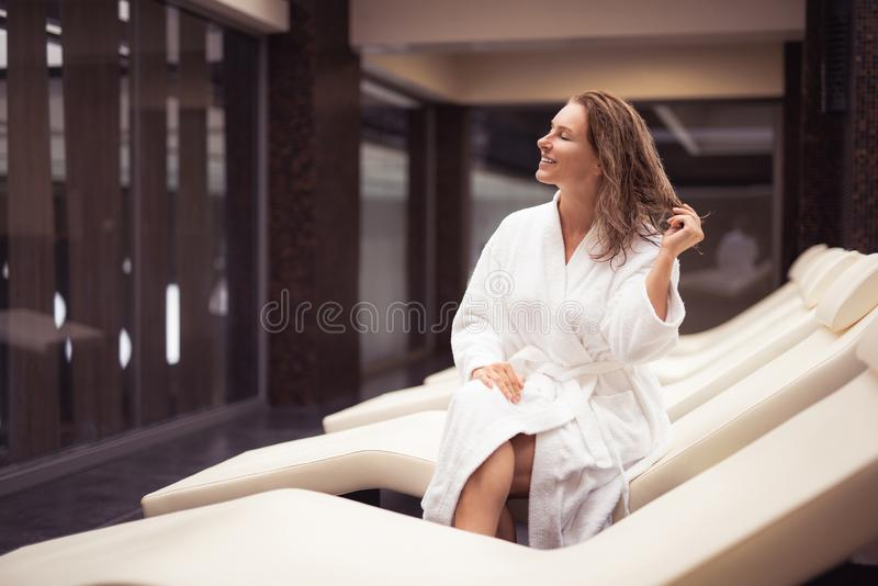 Le milieu joyeux a vieilli la femme dans le peignoir détendant au salon de station thermale image stock