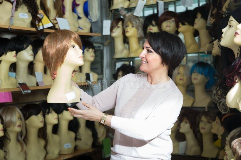 Le milieu positif a vieilli le client féminin sélectionnant la perruque naturelle de cheveux photographie stock libre de droits