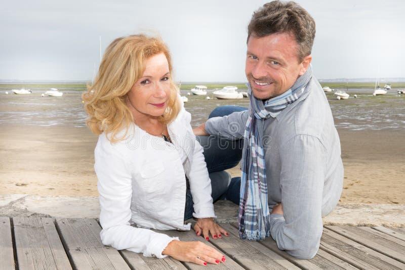 Le milieu romantique a vieilli le coucher du soleil de attente de couples sur la plage image libre de droits