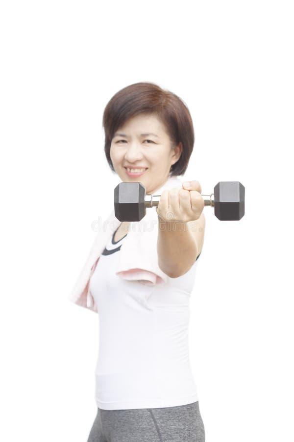 Le milieu sain de forme physique a vieilli le poids de levage heureux de femme asiatique photo stock