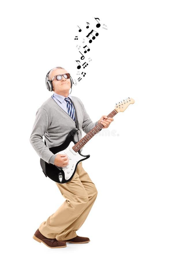 Le milieu a vieilli l'homme jouant la guitare et les notes musicales autour photos libres de droits