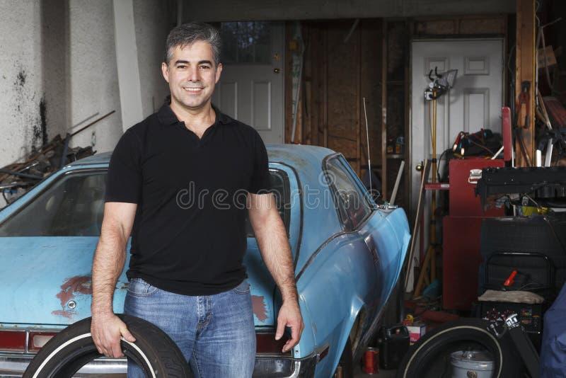 Le milieu a vieilli l'homme tenant le pneu en dehors de son garage images libres de droits