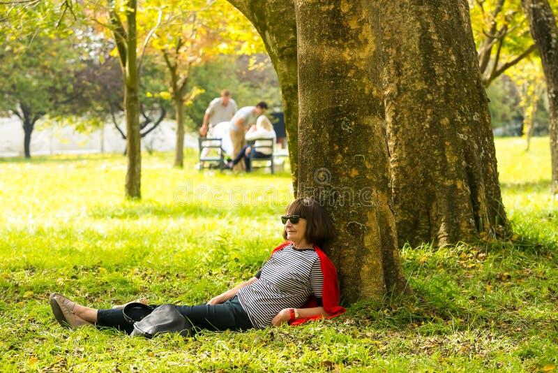 Le milieu a vieilli la dame se trouvant contre un arbre à la sculpture fa en hiver photos stock