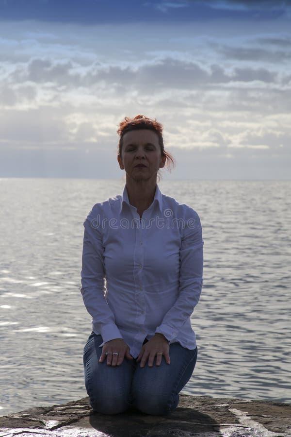 Le milieu a vieilli la femme au bord de la mer exécutant le yoga image stock