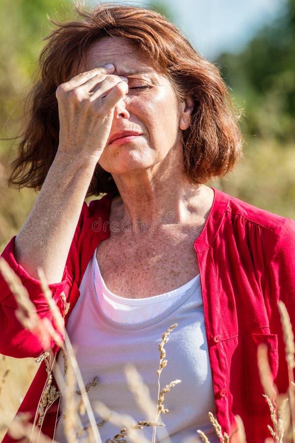 Le milieu a vieilli la femme ayant la rhinite, allergies dehors image stock