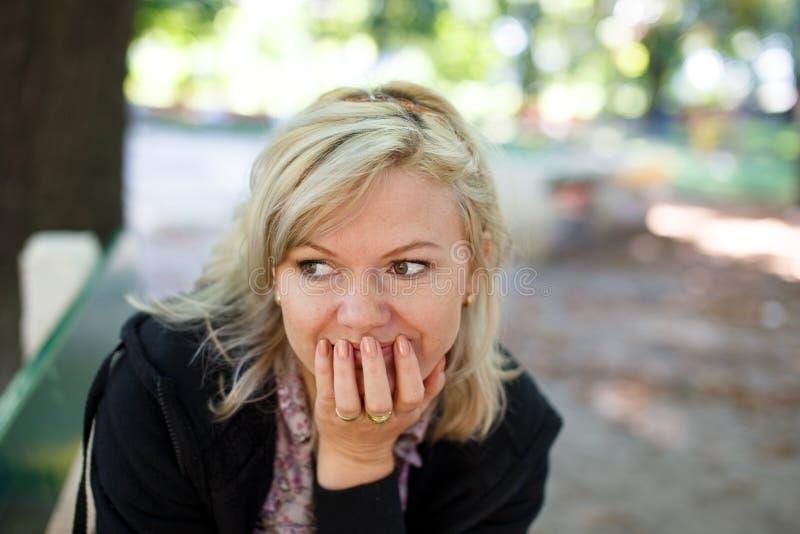 Le milieu a vieilli la femme blonde en parc regardant loin images libres de droits