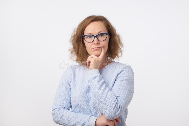 Le milieu a vieilli la femme européenne en verres bleus pensant et regardant l'appareil-photo, confus à une idée images libres de droits