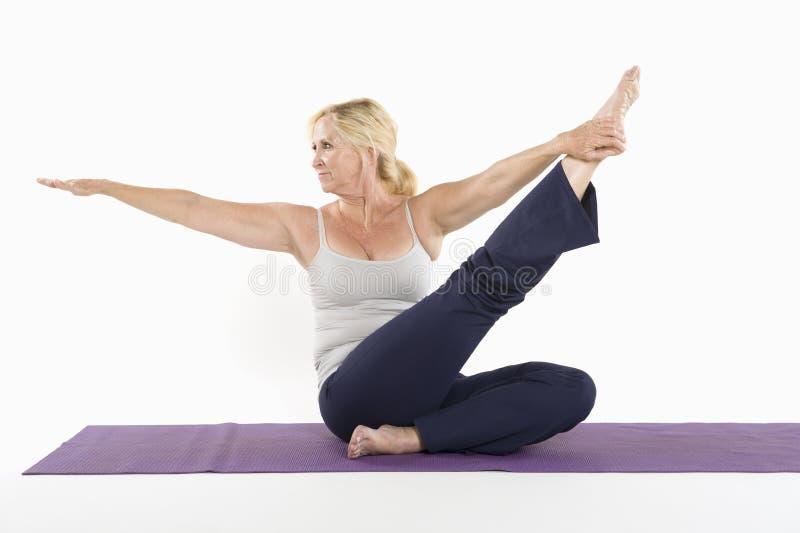 Le milieu a vieilli la femme faisant le yoga au-dessus du fond blanc photographie stock